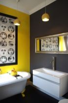 a-whimsical-bathroom-with-grey-and-yellow-walls-white-appliances-yellow-pendant-lamps-and-a-bold-and-quirky-artwork