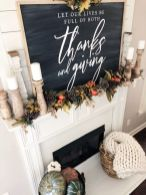 a-woodland-Thanksgiving-mantel-with-a-chalkboard-greenery-pumpkins-pinecones-candles-in-wooden-candleholders