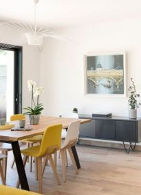 an-airy-modern-dining-room-with-a-grey-storage-unit-a-dining-table-yellow-and-white-chairs-and-a-pretty-retro-chandelier
