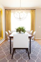 an-eclectic-and-chic-dining-rom-with-a-wooden-table-acrylic-and-upholstered-chairs-a-sphere-pendant-lamp-yellow-curtains-and-a-large-mirror