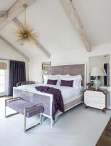 an-eclectic-bedroom-with-a-lavender-bed-and-an-upholstered-bench-a-sunburst-chandelier-wooden-beams-and-purple-and-white-bedding