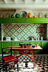 an-eclectic-kitchen-with-bold-green-cabinets-bright-printed-tiles-on-the-backsplash-a-wooden-table-and-a-chair-plus-colorful-tableware