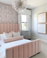 an-elegant-and-laconic-feminine-bedroom-with-a-wallpaper-wall-a-pink-bed-a-catchy-chandelier-and-abstract-artworks