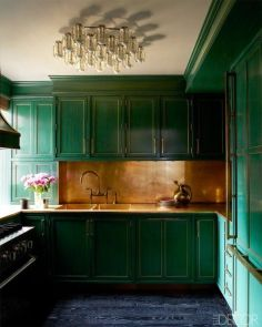 an-emerald-kitchen-with-a-gold-backsplash-and-countertops-and-a-refined-and-chic-chandelier-is-elegant-and-vintage-like