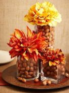 glass-vases-filled-with-acorns-and-with-bright-blooms-on-top-are-a-lovely-rustic-centerpiece-idea-for-Thanksgiving