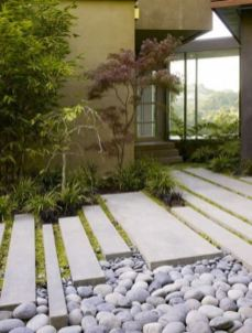 pebbles-long-and-narrow-tiles-grass-and-mini-Japanese-trees-at-the-entrance-make-the-front-yard-very-elegant-sleek-and-catchy