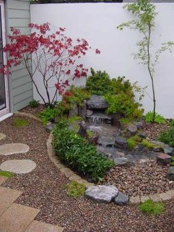 pebbles-tiles-a-waterfall-on-rocks-shrubs-and-mini-thin-trees-will-make-your-outdoor-space-super-inspiring-and-calming