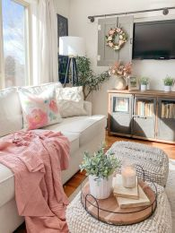 pink-and-floral-textiles-potted-greenery-and-faux-blooms-and-candles-make-the-neutral-living-room-more-chic