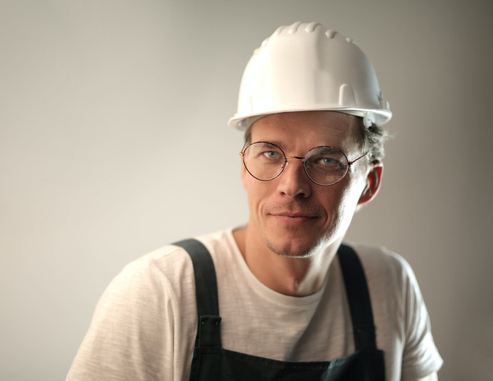 smiling male worker in construction helmet in studio