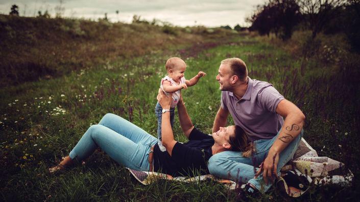 kisbaba a szüleivel nevet a réten