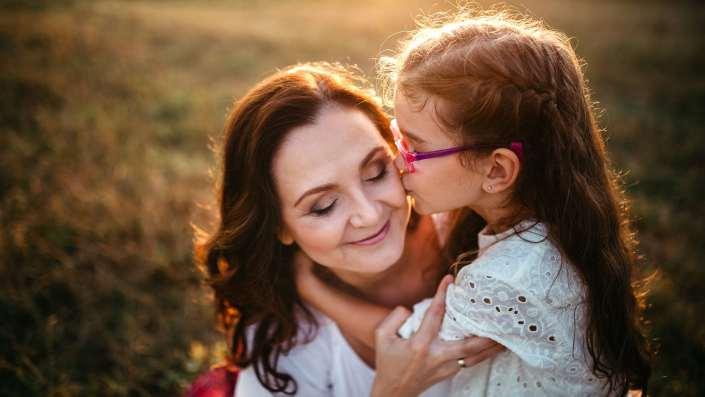 Anyuka és kislánya ölelik egymást egy mezőn