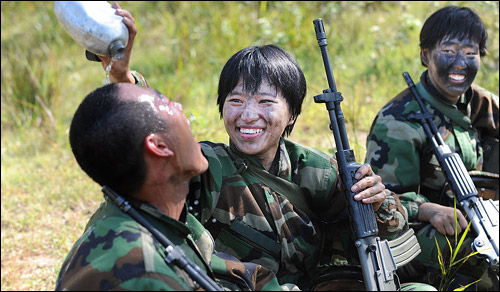 A female soldier cools a male comrade with water after atomic, biological and chemical weapons training at the Non-Commissioned Officer Academy in Iksan, North Jeolla Province on Sept. 19.