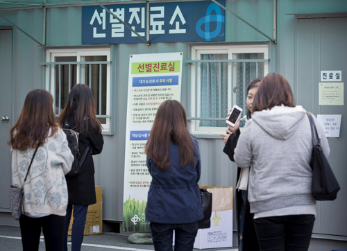 Students look at instructions in front of a makeshift clinic at Konkuk University in Seoul on Thursday.