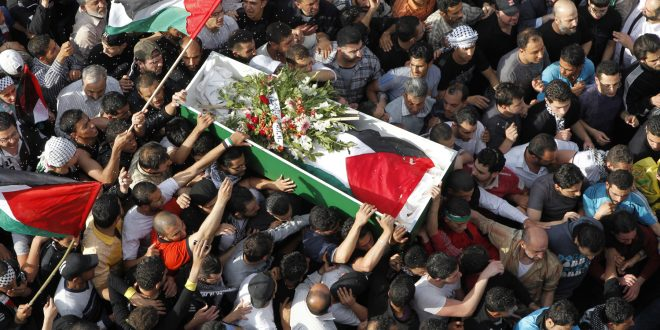 Image: Palestinians carry the coffin of a person, who was shot dead yesterday by Israeli soldiers during clashes at Majdal Shams, during a funeral in al-Yarmouk camp near Damascus