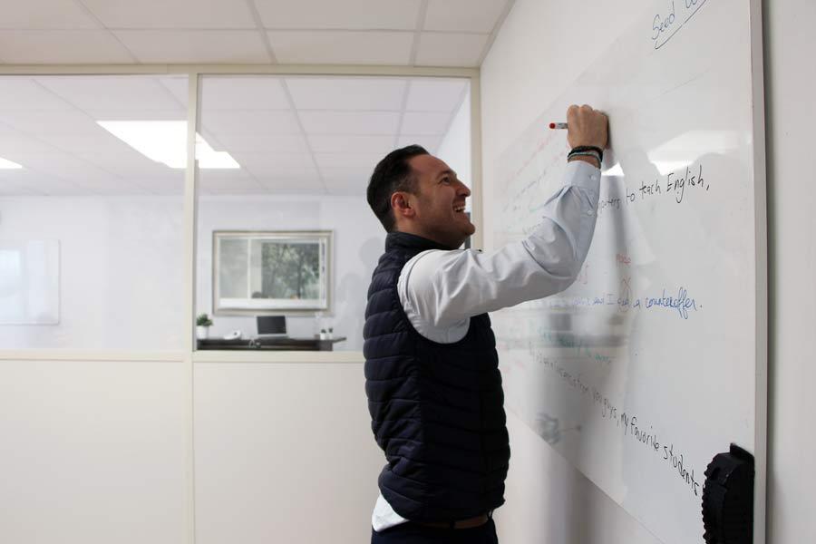 Un stagiaire écrit au tableau blanc en plein cours d'anglais