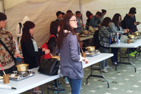 Students prepare their free samples of Paldo ramen at cooking stations provided. (PHOTO: Charles Ian Chun)