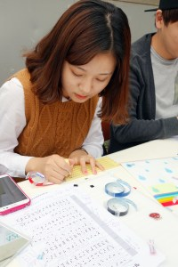 2nd-year special education major Kim Cho-rok embosses name labels in Braille for fellow students.