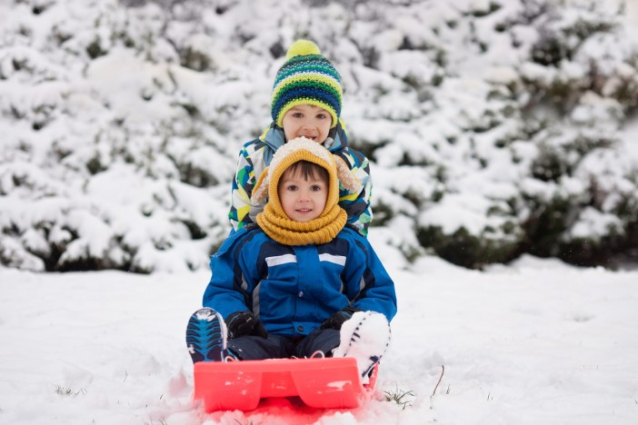 Two kids sledging in the snow