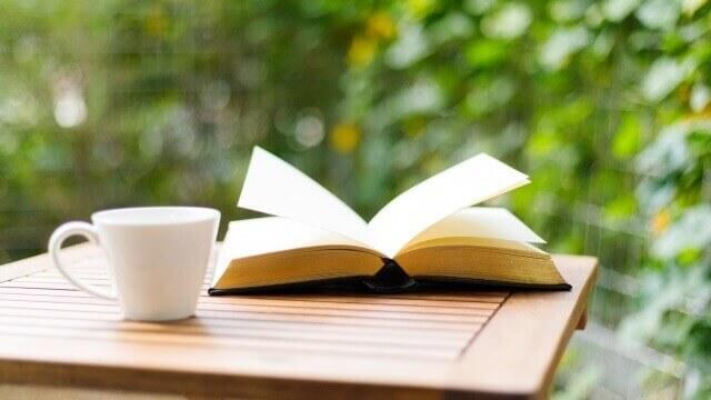 天気の良い日に庭で読書をするイメージ「本とコーヒー」