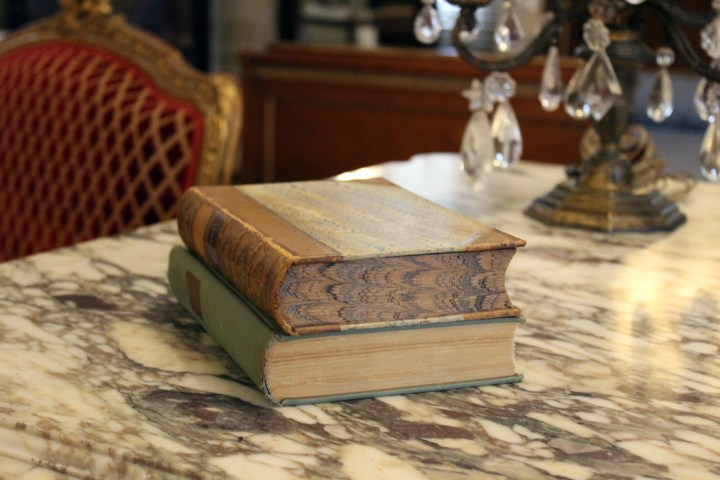 Rosecliff Mansion - Newport RI | Vintage books--one with a marbled edge--are stacked and ready for the bedroom guest's repose.