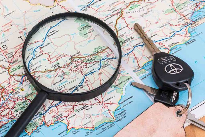 Magnifying glass and car keys on map