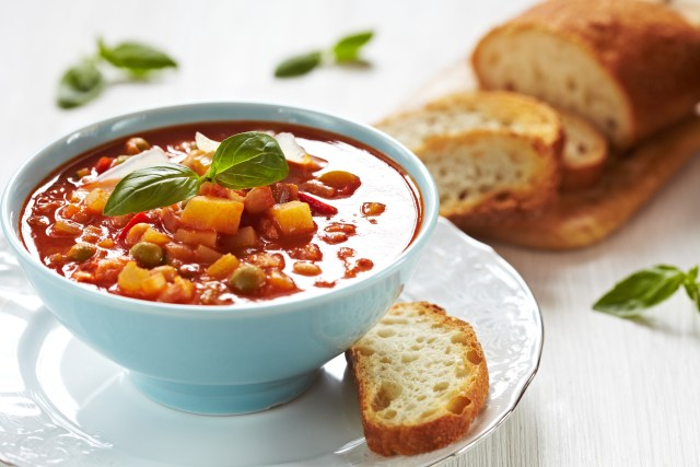 Bowl of minestrone soup with a slice of bread on the side