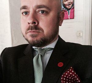 Med rød kapp på jakkeslaget - og datteren min i bakgrunnen...