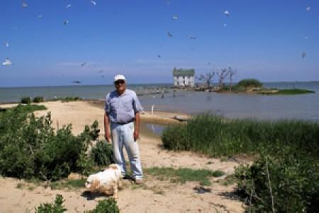 Stephen White avec en arrière-plan son île