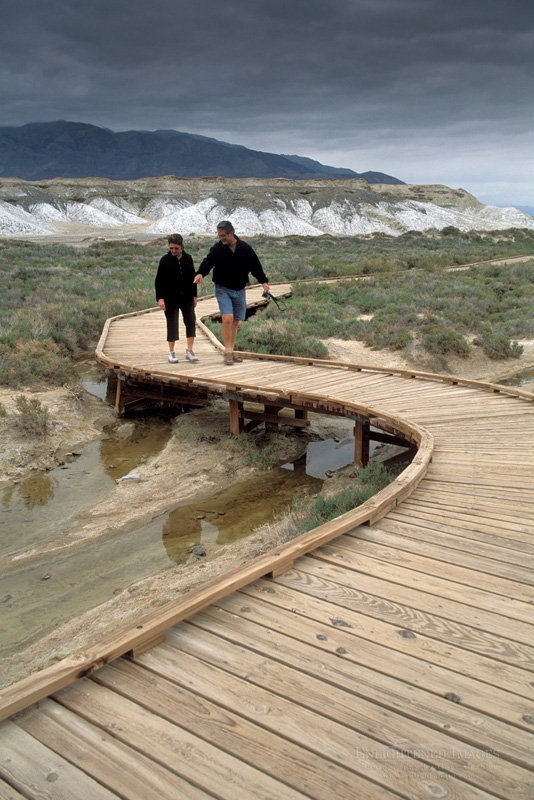 Photo: Tourists walking on wooden boardwalk nature trail path at Salt Creek, Death Valley National Park, California