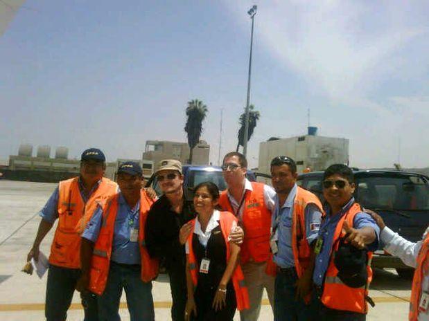 (Foto Radio Oxigeno) Bono posa al lado de un grupo de empleados aeroportuarios en Lima.