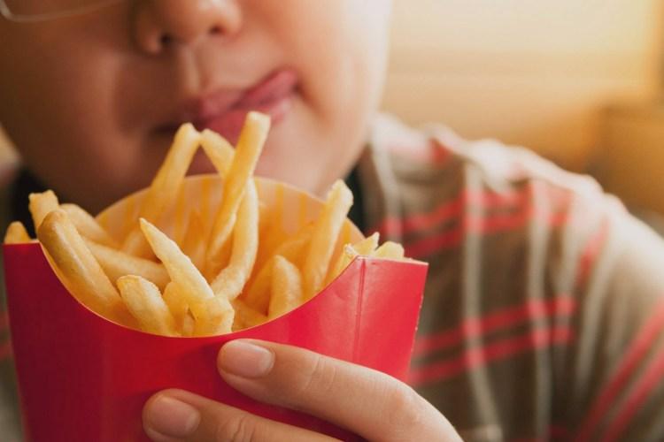 Niño con sobrepeso y papitas