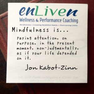 "Jon Kabot-Zinn quote on an Enliven Wellness Coaching sticky note, ""Mindfulness is paying attention, on purpose, in the present moment, non-judgmentally, as if your life depended on it."""