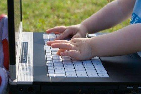 manos bebe escribiendo ordenador portatil