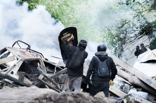 fights about the eviction of barricades on 26/04/2018. two Zadists standing at the big barricade holding improvised shields, and looking at the tear gas cloud in front of them