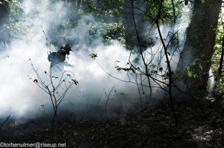 fights about the eviction of barricades on 27/04/2018. Zadist with gas mask running through a tear gas cloud in the woods trying to shoot back canisters with a tennis racket