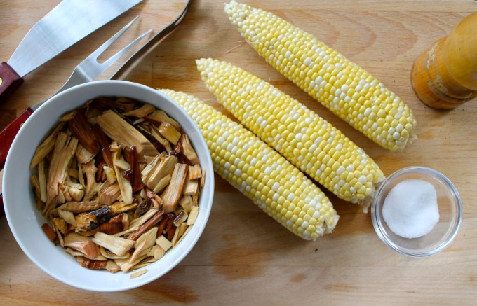 wood chips, corn on the cob, ready for grilling boneless pork chops with BBQ sauce