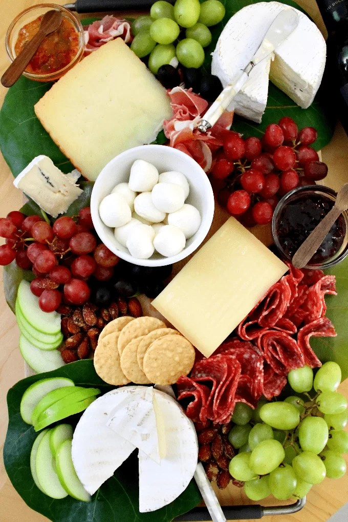 Cheeseboard including charcuterie, grapes, marmalade, almonds, olives and crackers.