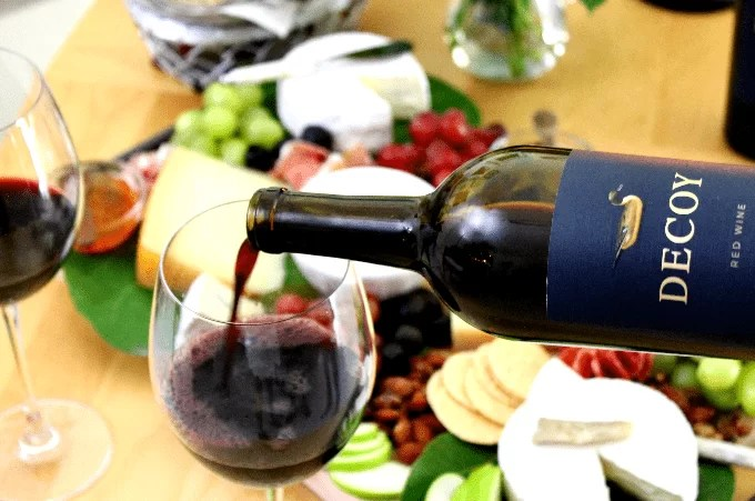 red wine being poured on a glass with cheese tray in the background.