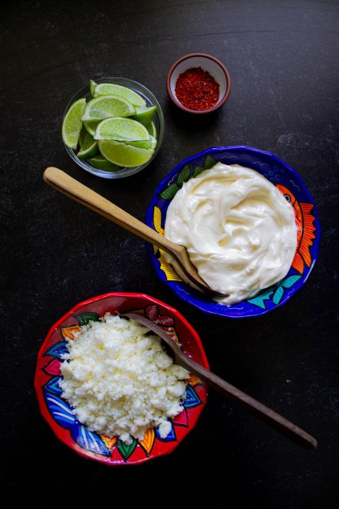 toppings para ensalada de maíz estilo mexicano, incluyendo mayonesa, chile picante, limón en gajos, y queso fresco