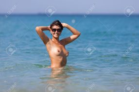 Girl at the sea. Naked young woman with arms raised looking at camera through sunglasses