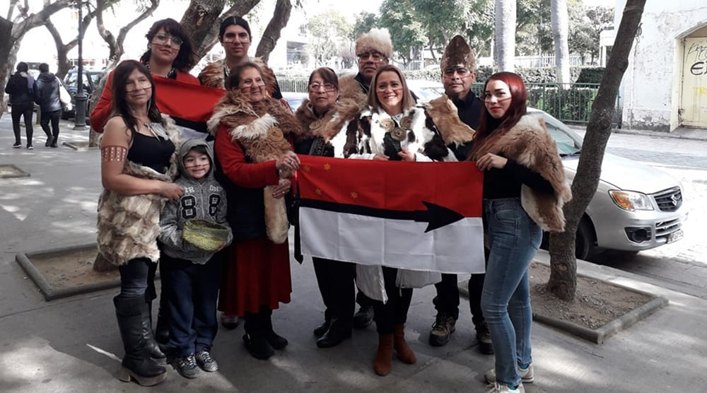 contemporary intergenerational group of selk'nam community members pose with flag