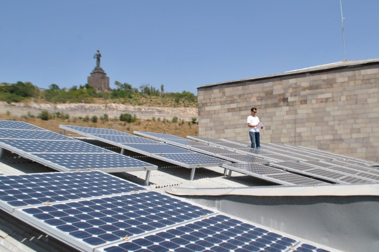Solar Panels in grassy sunny area, person stands at the back