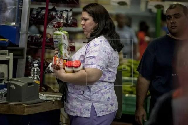Una mujer carga en sus manos alimentos dentro de un supermercado privado en la ciudad de Caracas (Venezuela). EFE/Archivo