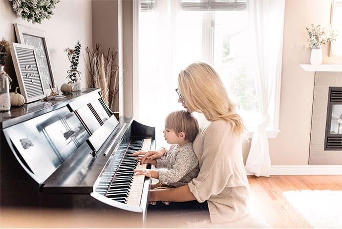 """Photo d'une mère et de son fils sur un piano droit pour l'article """"Bien Choisir Son Clavier"""""""