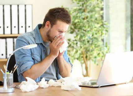 A man sneezing, suffering from allergies.