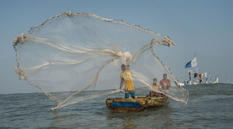 A fisherman casts his net in the waters