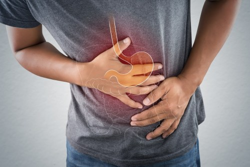 Acid reflux or Heartburn, The photo of stomach and internal organs is on the men's body against gray background, Stomach ache, Bad health, Male anatomy concept.