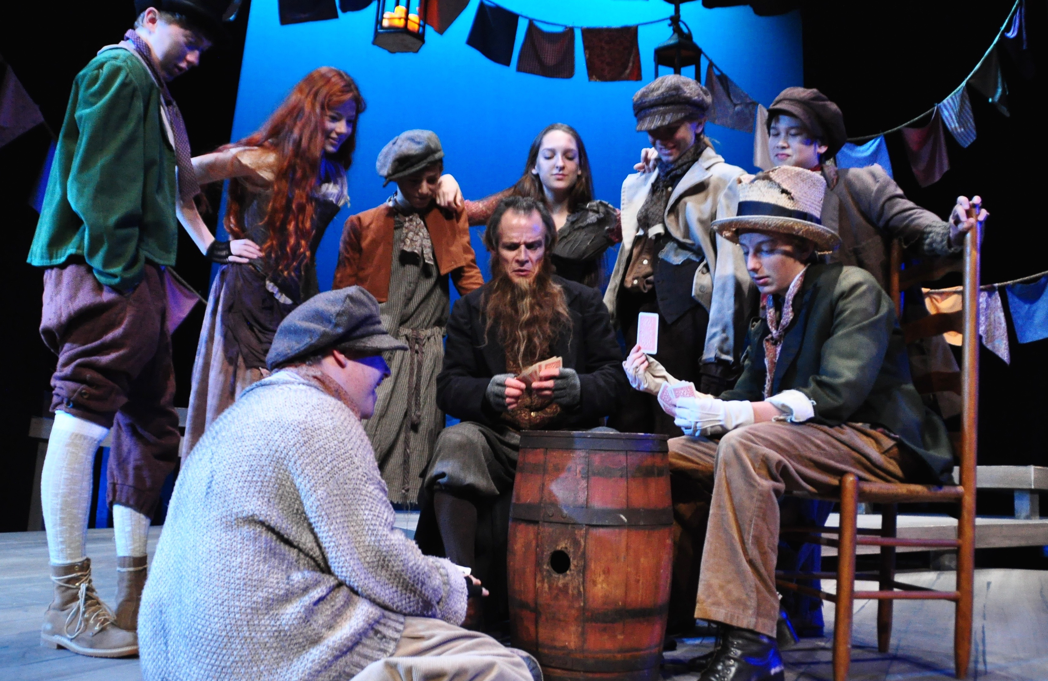 They're playing with a full deck but the game isn't fair. Fagin (James FitzGerald, bearded) runs the show in this illicit corner of London and young folks like the Artful Dodger (Simon Colker, R, in the torn hat) are his minions.