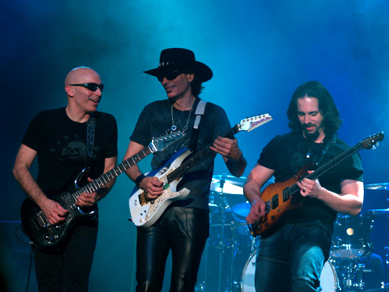(l. to r.) Joe Satriani, Steve Vai, and John Petrucci on the 2006 G3 tour in Melbourne, Australia. Phil Collen of Def Leppard joins Satriani and Petrucci for this year's G3. Photo: Mandy Hall and Wikipedia.