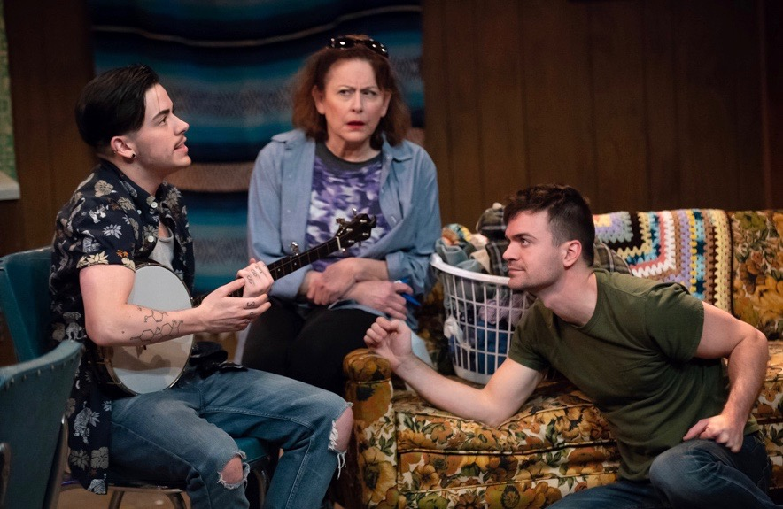 There's nothing like banjo music to bring a fractured family together—especially banjo music from a trans teen! Max (Liam Ezra Dickinson, L) gamely gives Mom's latest scheme a try.